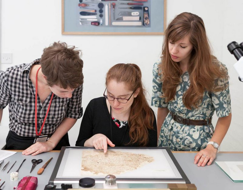 Conservators Rebecca Goldie, Mary French, and Emma Nichols examine a Lewis-Gibson fragment