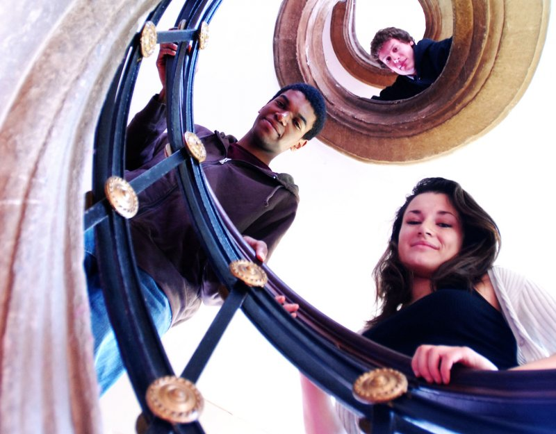 Students climbing a spiral staircase in a College