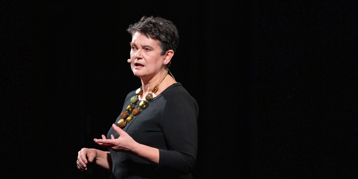 Professor Diane Coyle standing on a stage speaking