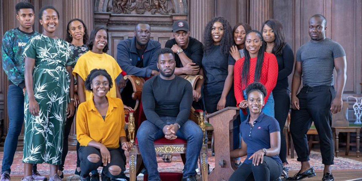 Stormzy seated and surrounded by students from the University of Cambridge Afro-Caribbean Society