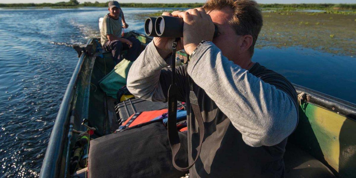 Rewilding Europe. Man in a speedboat looking left through binoculars.