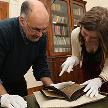 Paul Russell, Professor of Celtic, examining a text with a colleague